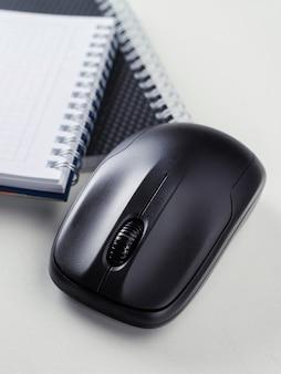 Biały drewniany stół z długopisem, myszką, notatnikiem. obszar roboczy z miejscem na kopię.