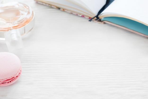 Biały drewniany stół z kobiecymi akcesoriami. skopiuj miejsce na stole z notatnikiem, makaronikiem i perfumami. młode romantyczne dziewczyny w miejscu pracy