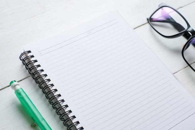 Biały drewniany stół z notatnikiem, okularami, długopisem, ozdobnymi roślinami. widok z góry z miejscem na kopię, układ płaski.