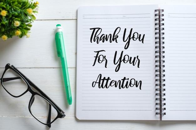 """Biały drewniany stół z okularami, długopisem, ozdobnymi roślinami i notesem z napisem """"dziękuję za uwagę"""". widok z góry z miejscem na kopię, układ płaski."""