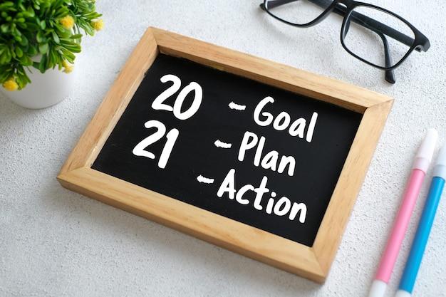 Biały drewniany stół z okularami, długopisem, ozdobnymi roślinami i tablicą z napisem plan działania 2021 goals. widok z góry z miejscem na kopię, układ płaski.