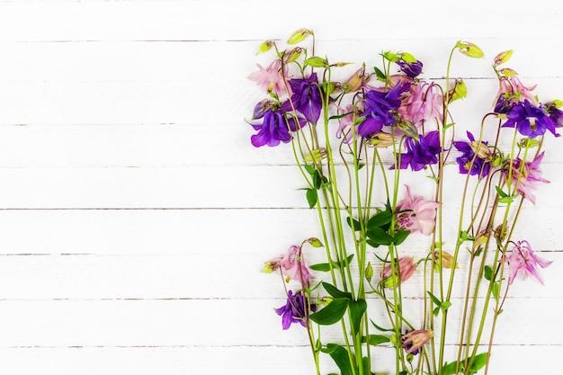 Biały drewniany stół z różowymi i niebieskimi kwiatami orlików z widokiem z góry na miejsce na kopię