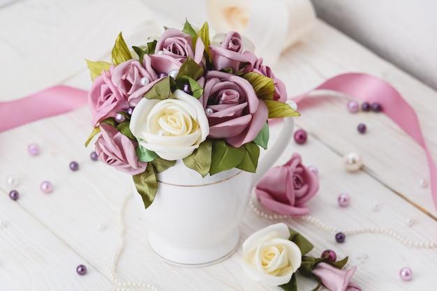 Biały drewniany stół z różowymi kwiatami, wstążkami i koralikami. styl ślubu