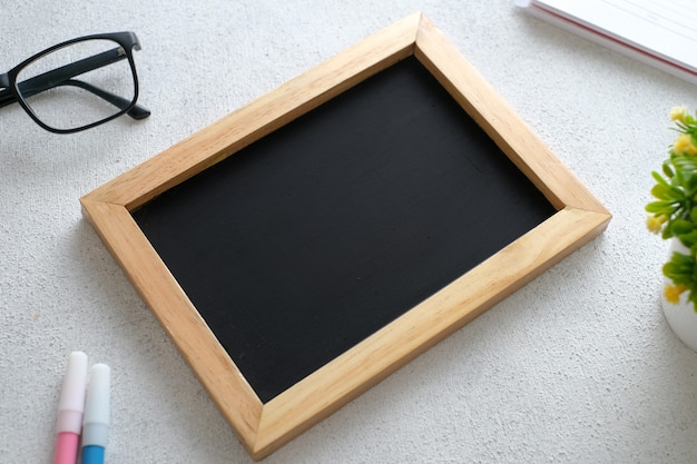Biały drewniany stół z tablicą, okularami, długopisem, roślinami ozdobnymi. widok z góry z miejscem na kopię, układ płaski.