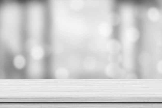 Biały drewniany tabletop nad plamy bokeh światła białym tłem. pusta drewniana półka do prezentacji produktów, banerów lub makiet.