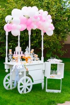 Biały drewniany wózek ze słodyczami ozdobiony balonami na zielonej trawie