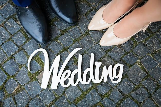 Biały drewniany znak na weselu to para stóp