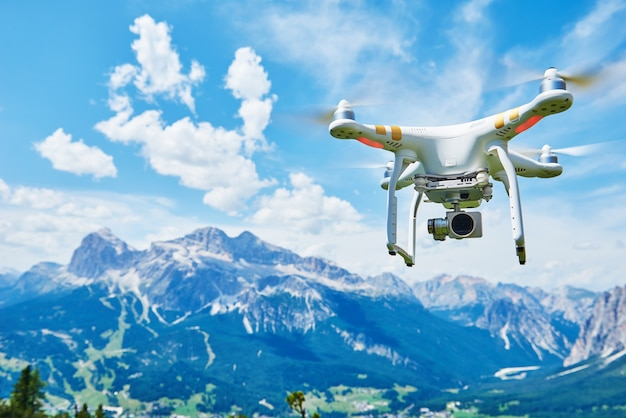 Biały dron dron z aparatem cyfrowym o wysokiej rozdzielczości lecący po błękitnym niebie nad górą