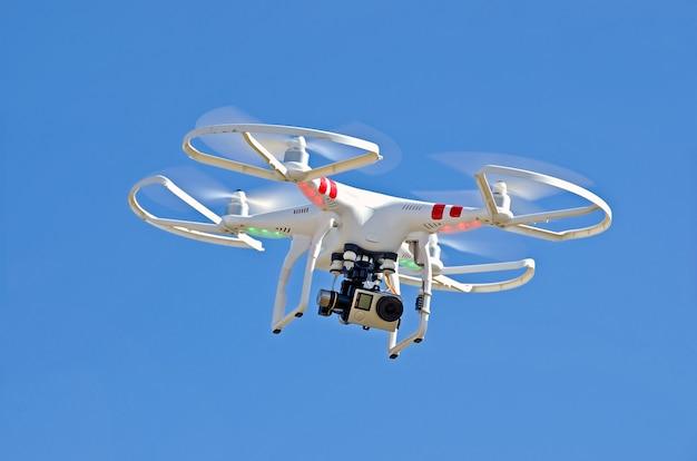 Biały dron unosi się na niebieskim niebie