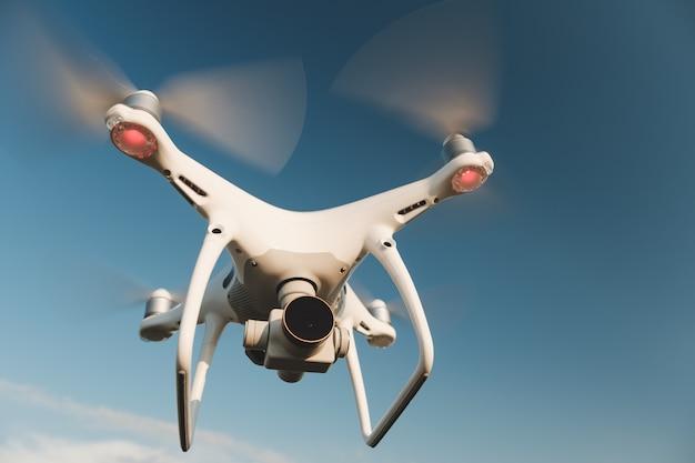 Biały dron unoszący się na jasnym błękitnym niebie