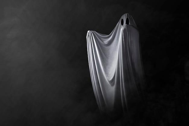 Biały duch nawiedzający na ciemnym tle. koncepcja halloween