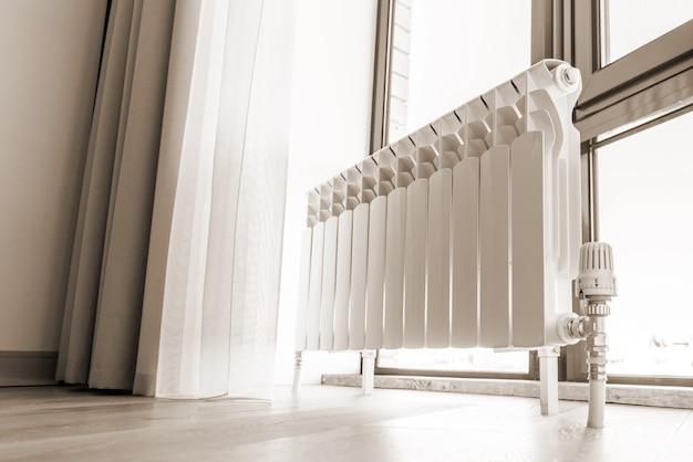 Biały duży grzejnik w pobliżu okna w nowoczesnym pokoju, w odcieniach sepii