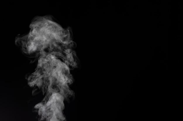 Biały dym na czarnym tle. wyobrażony dym na ciemnym tle. abstrakcyjne tło, element projektu, do nakładania na zdjęcia