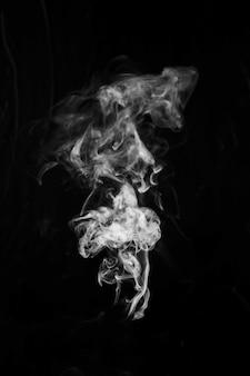 Biały dym na środku czarnego tła