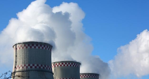 Biały dym pochodzi z rur na tle błękitnego nieba. problem szkodliwych emisji i zanieczyszczenia powietrza w populacji ekologicznej dużych miast w koncepcji ekologicznej