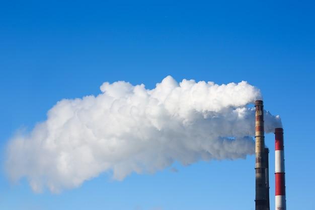 Biały dym pochodzi z rur na tle błękitnego nieba