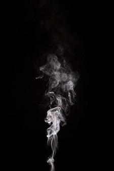 Biały dym podnoszenie na czarnym tle z miejsca na kopię