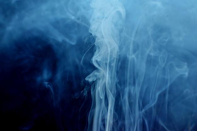 Biały dym przepływ na ciemnym tle.