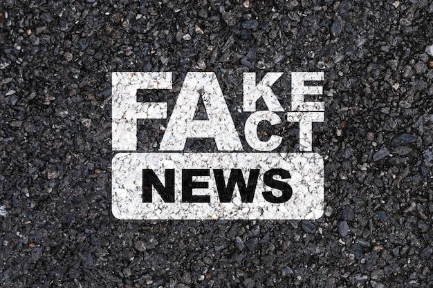 Biały ekran drukowania wiadomości fake and fact na asfaltowej drodze betonowej.