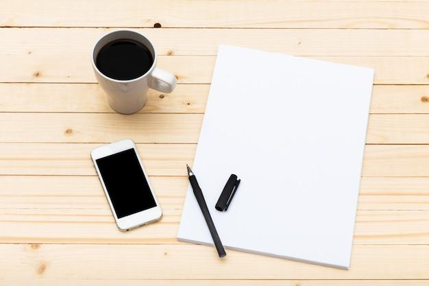 Biały ekran smartfona na drewnianym stole, widok z góry