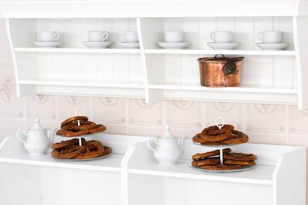 Biały ekspres do kawy z pieczonymi precelkami w białej kuchni. zdjęcie wysokiej jakości