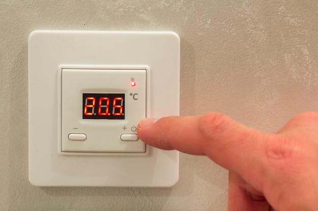 Biały elektroniczny programowalny cyfrowy termostat na światło ściany kopii przestrzeni tle. klimatyzacja, komfortowa temperatura w domu, koncepcja oszczędzania energii.