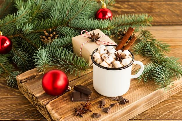 Biały emaliowany kubek z gorącą czekoladą lub kakao z piankami marshmallow na drewnianym podeście na tle zielonej gałęzi świerka.