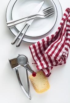 Biały emaliowany pusty talerz na stole z czerwoną serwetką w kratkę i parmezanem