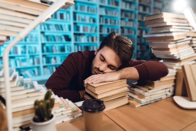Biały facet otoczony książkami w bibliotece. student śpi
