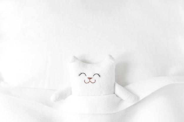 Biały filcowy kot śpi na łóżku pod białym kocem.