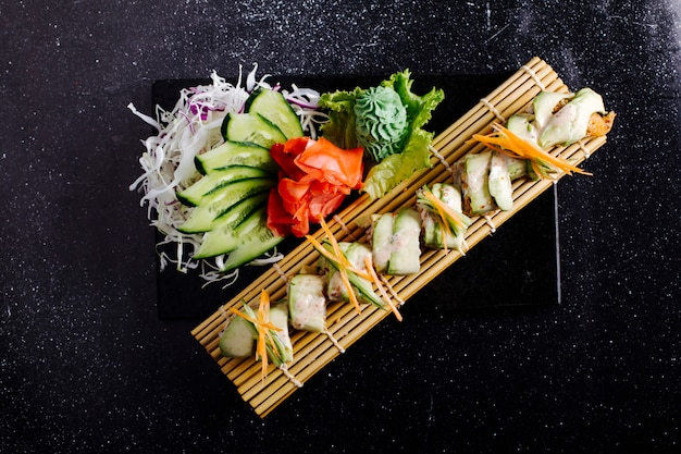 Biały filet rybny na macie do sushi z imbirem, wasabi i ogórkiem na czarnym stole.