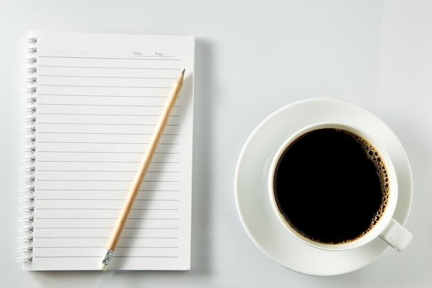 Biały filiżanka kawy ranek na drewnianym stole z notatnikiem