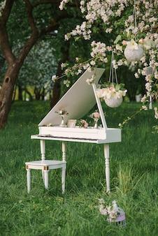 Biały fortepian stoi wiosną w kwitnących sadach jabłoniowych. dekoracje ślubne lub urodzinowe romantyczne i delikatne