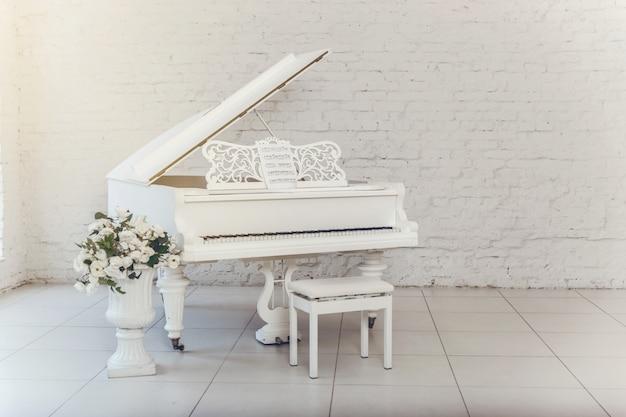 Biały fortepian w dużym białym pokoju stoi pośrodku pokoju