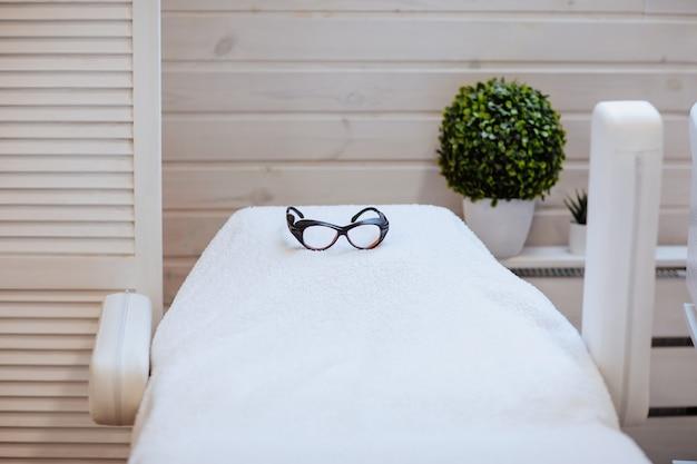 Biały fotel medyczny z czarnymi okularami do zabiegu depilacji i zieloną rośliną z drewnianą ścianą. skopiuj miejsce.