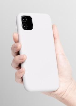Biały futerał na telefon komórkowy w ręku prezentacja produktu b