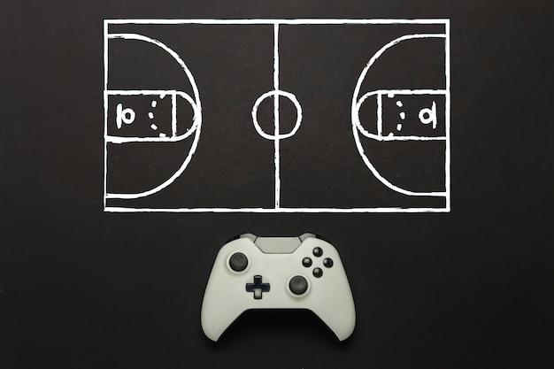 Biały gamepad na czarnym tle. dodano schemat boiska do koszykówki. taktyka gry. gra koncepcyjna koszykówki na konsoli, gry komputerowe. leżał płasko, widok z góry.