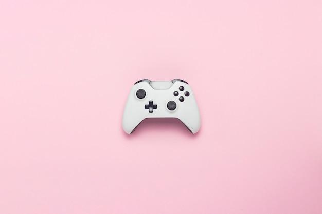 Biały gamepad na różowym tle. gra koncepcyjna na konsoli, gry komputerowe. leżał płasko, widok z góry.