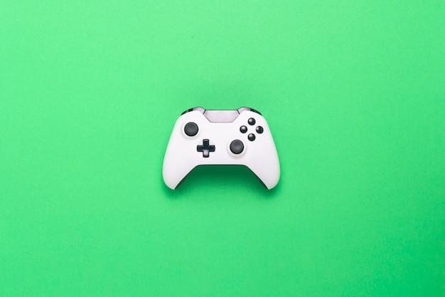 Biały gamepad na zielonym tle. gra koncepcyjna na konsoli, gry komputerowe. leżał płasko, widok z góry.