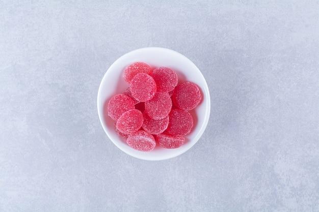 Biały, głęboki talerz pełen czerwonych słodkich cukierków z galaretką owocową na szarej powierzchni