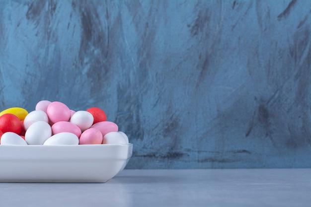 Biały głęboki talerz pełen kolorowych cukierków fasolowych na niebiesko-szarym stole.