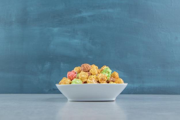 Biały, głęboki talerz słodkiego, wielobarwnego popcornu.