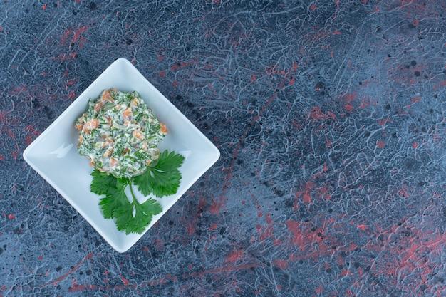 Biały głęboki talerz z pyszną sałatką i ziołami