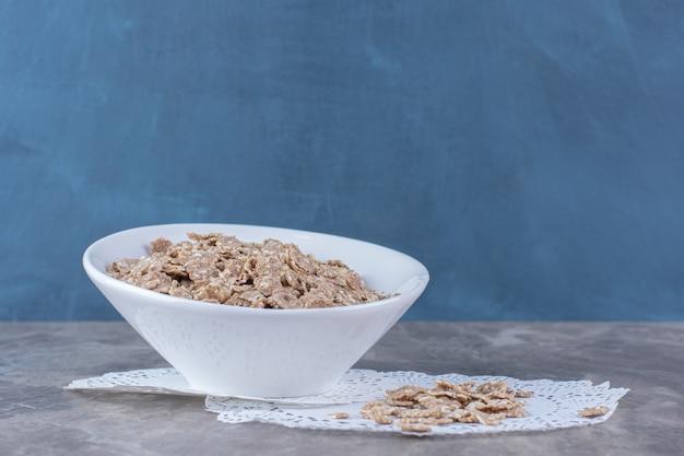 Biały głęboki talerz ze zdrowymi płatkami kukurydzianymi na szaro.