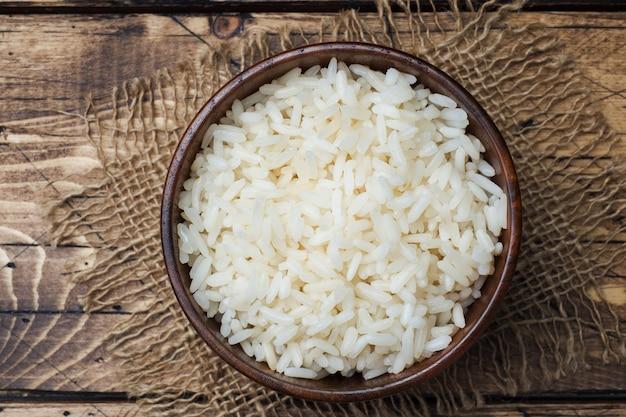 Biały gotowany ryż w drewnianej misce. styl rustykalny.
