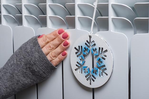 Biały grzejnik w domu z symbolicznym płatkiem śniegu