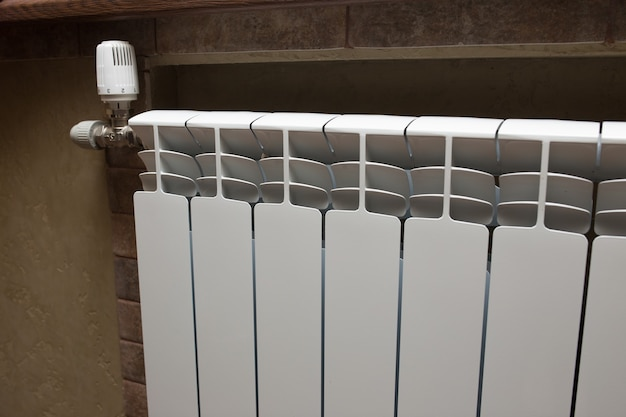 Biały grzejnik w łazience z bliska. ogrzewanie. kafelkowa szara ściana.