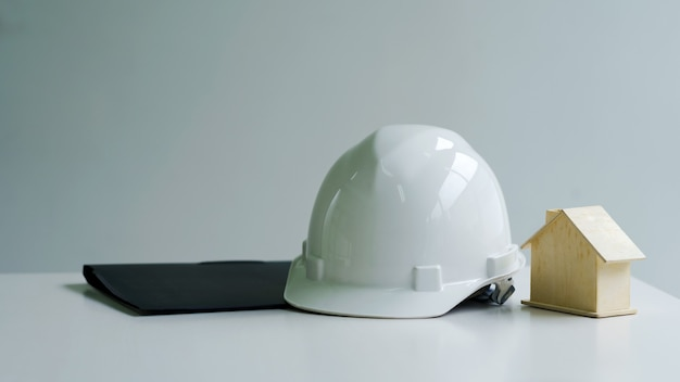 Biały hełm ochronny pracownika inżyniera domu umieścić na stole.
