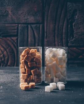 Biały i brązowy cukier w szklankach wodnych