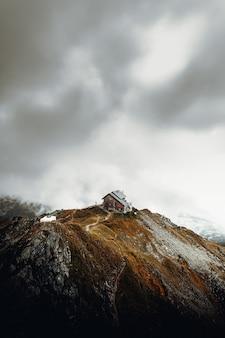 Biały i brązowy dom na szczycie brązowej góry pod białymi chmurami